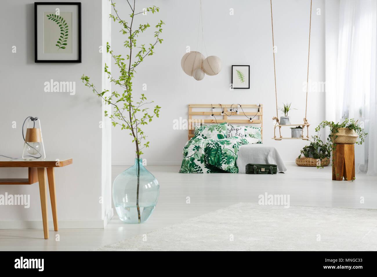 Chambre blanche avec des plantes vertes, lit en bois et ...