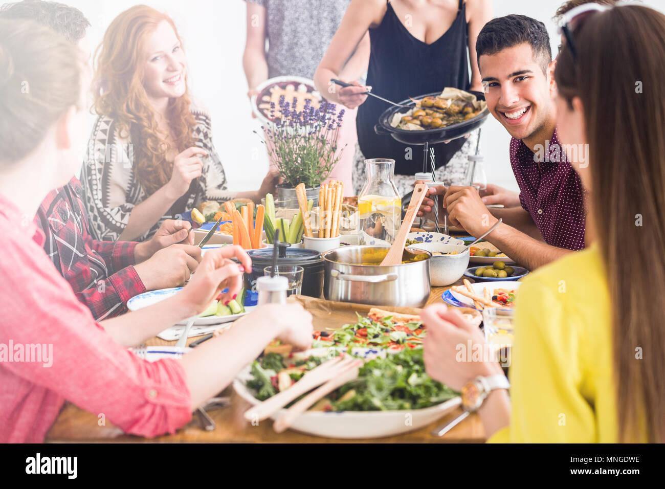 Les gens heureux faire cuire et manger ensemble vege fresh déjeuner à Friend's home Banque D'Images