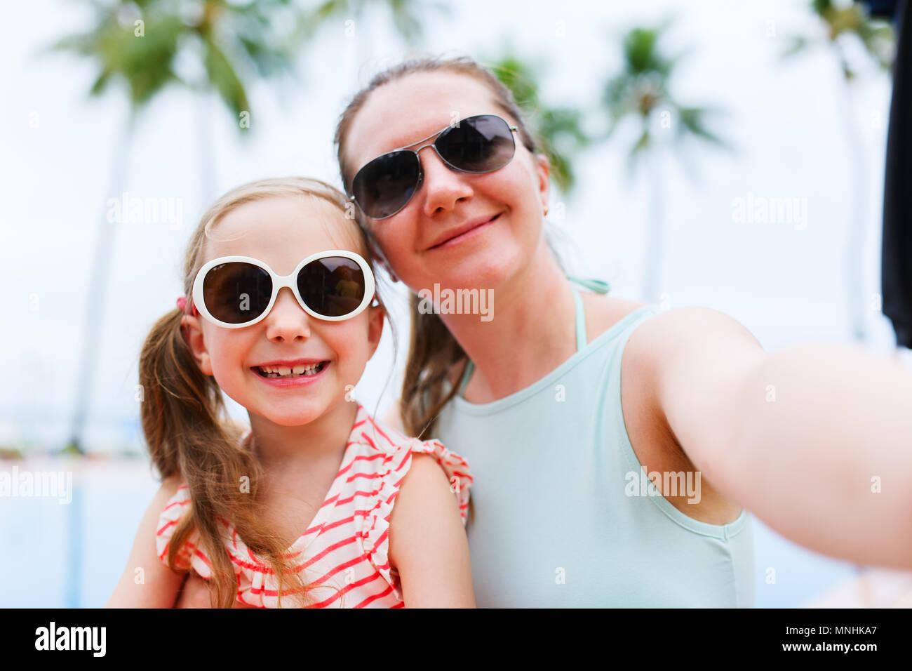 Famille heureuse mère et son adorable petite fille en vacances en tenant avec smartphone selfies Banque D'Images