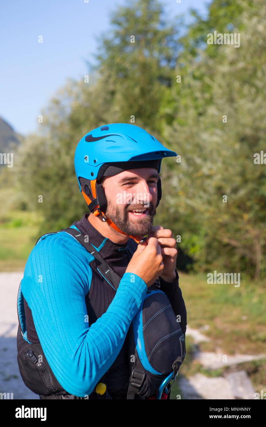 Kayakiste souriant avec barbe mise sur casque de sécurité avant de kayak dans la rivière Soca près de Bovec, littoral slovène, la Slovénie Photo Stock