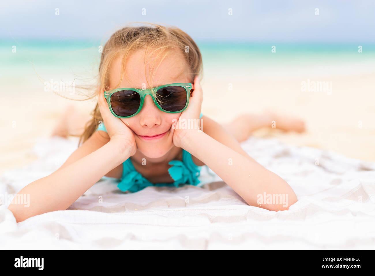 Adorable petite fille allongée sur une serviette de plage pendant ...