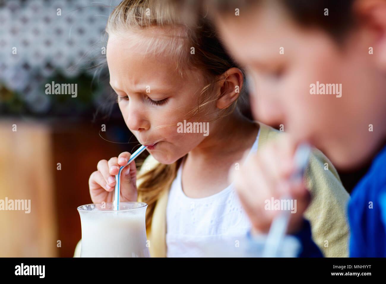 Les jeunes frère et sœur de lait frappé au café en plein air potable Photo Stock