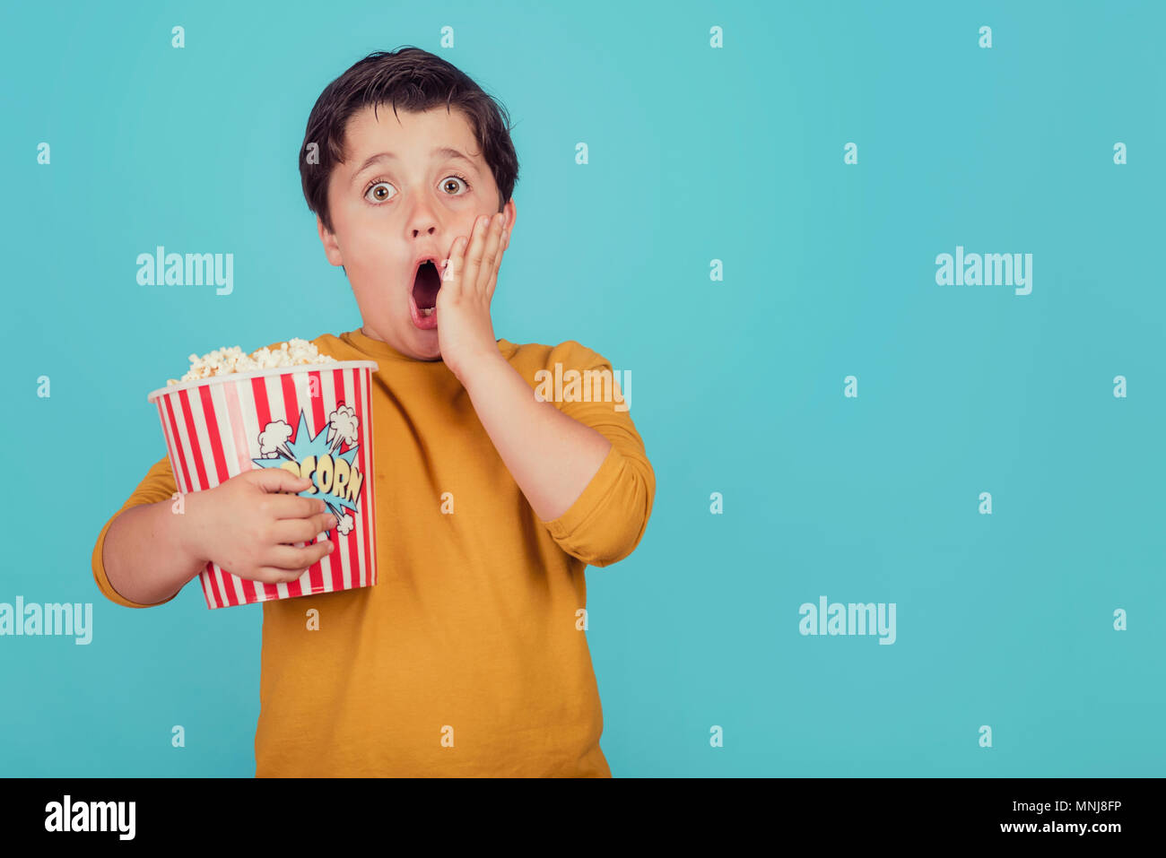 Surprise garçon avec popcorn on blue background Photo Stock
