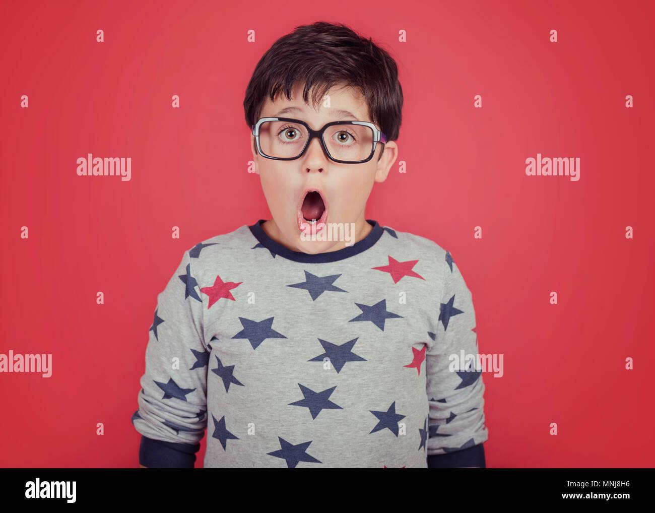 Surprise garçon avec des lunettes sur fond rouge Photo Stock