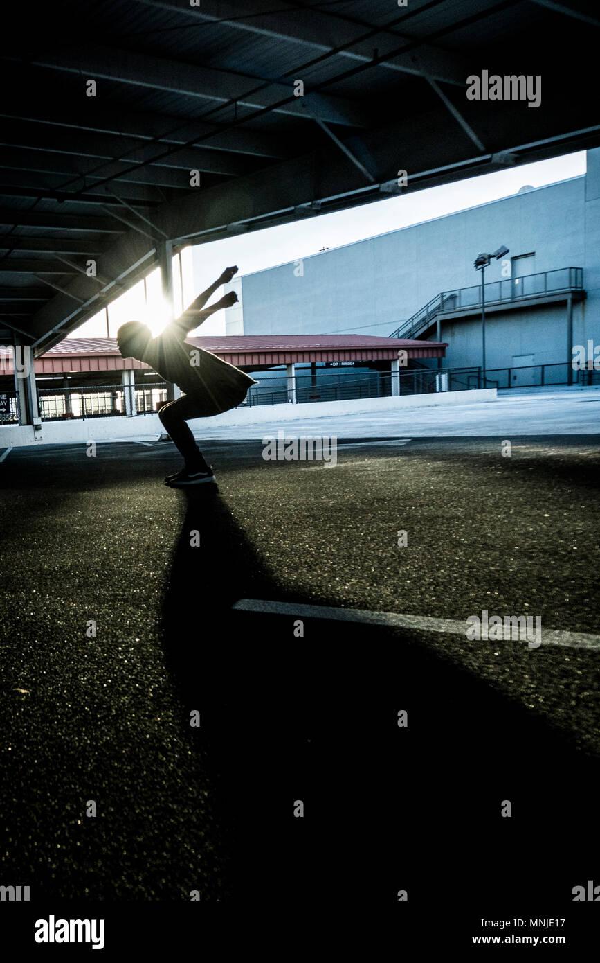 L'athlète du parc s'apprête à faire standing back flip dans parking en centre-ville de Denver, Colorado Photo Stock