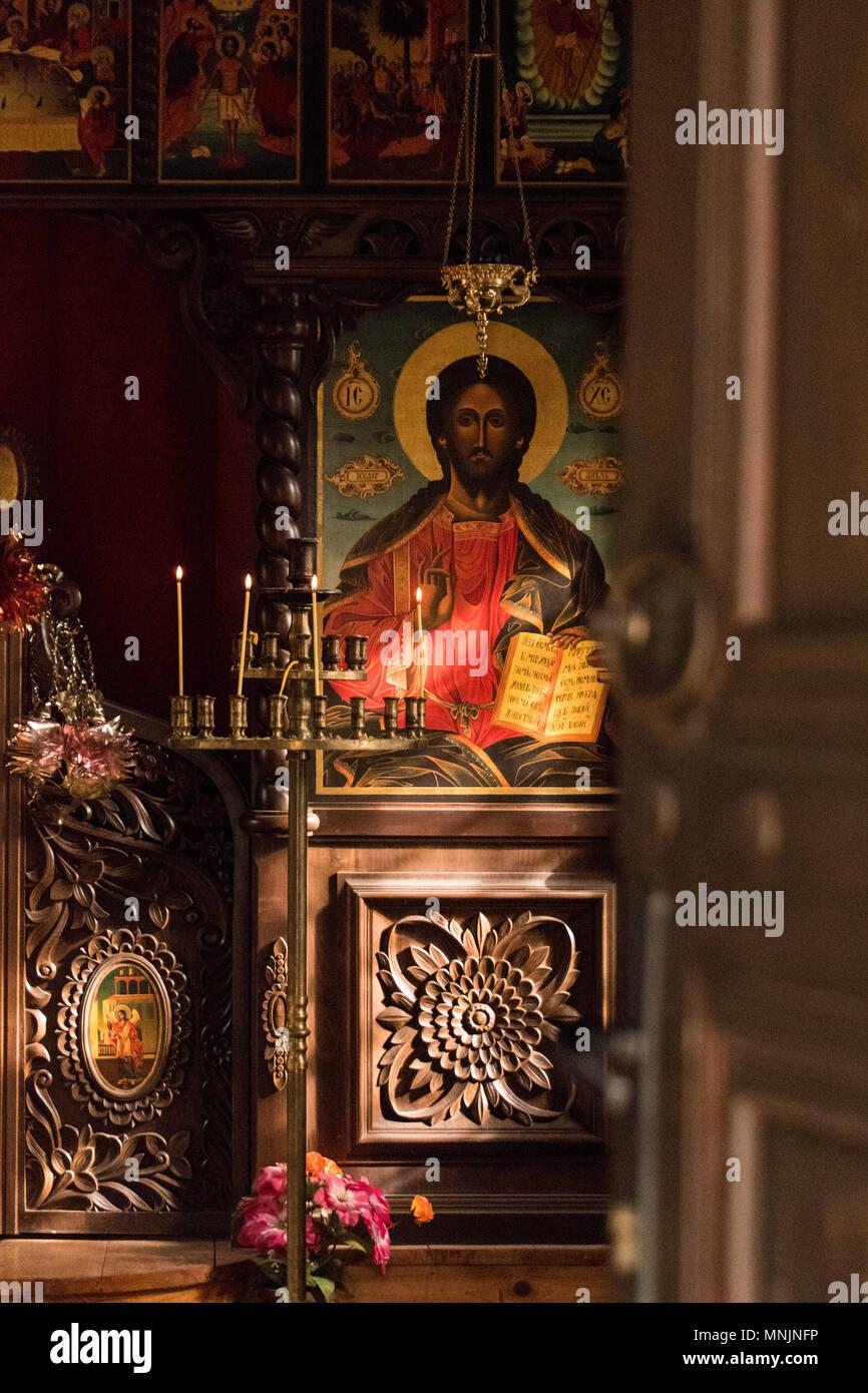 Rayons de lumière brillant onn une icône de Jésus Christ dans une église orthodoxe en Bulgarie, avec des bougies allumées en face d'elle Photo Stock