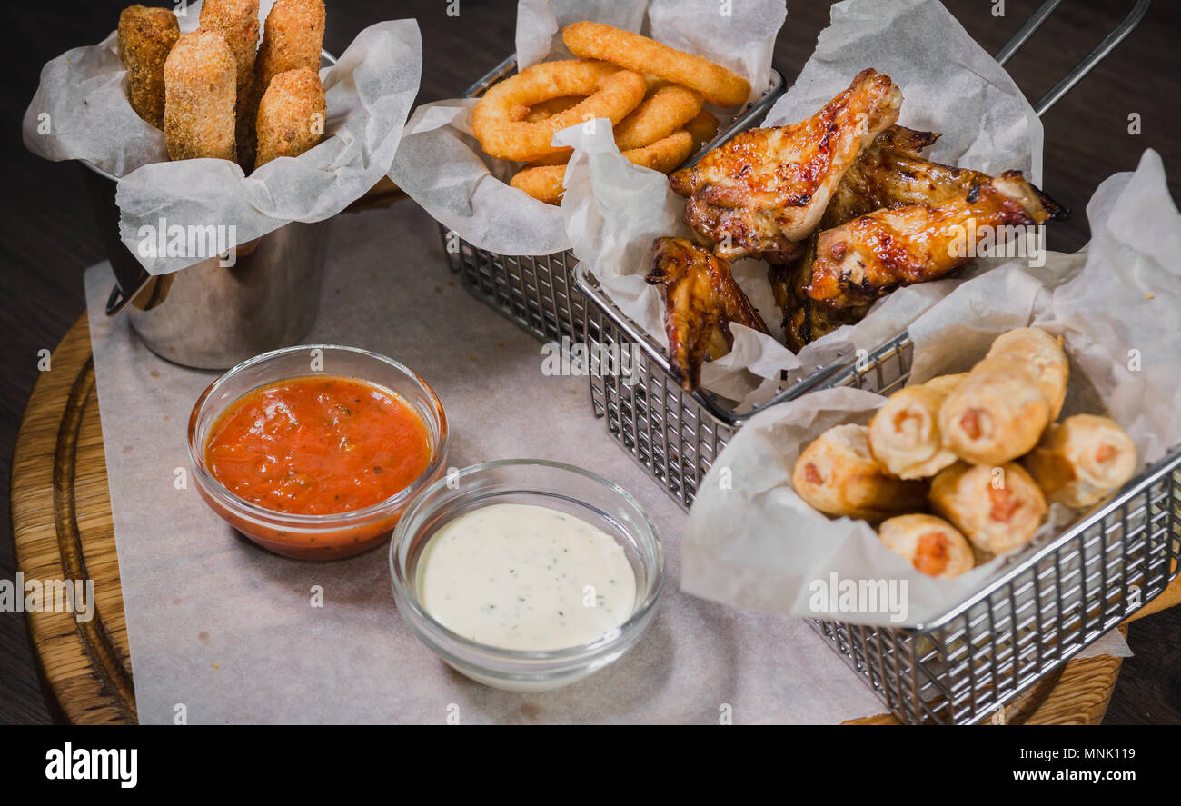 Snack pour la bière sous forme de fromage nuggets de poulet frit et anneaux de jambes Photo Stock