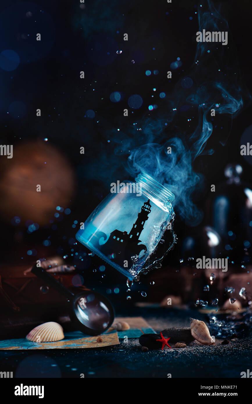 Phare dans un bocal de verre fwith mist, les projections d'eau, boussole, globe et coquilles sur un fond noir de fumée. Concept avec copie espace maritime. Ca Photo Stock