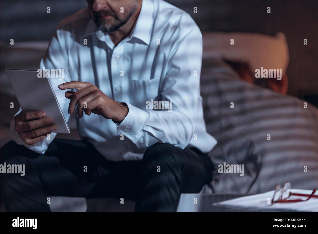 Low angle view of a mature homme assis sur un lit dans une chambre et la tenue d'une tablette dans sa main avec une femme dormir sous une couverture de lit dans un flou background Photo Stock