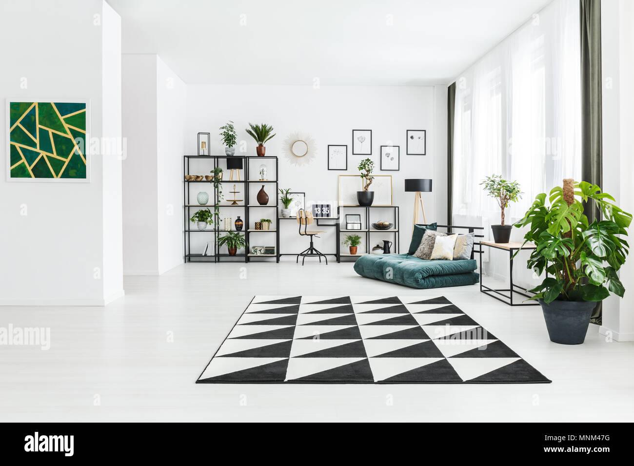 Et l'usine de peinture verte à l'intérieur spacieux appartement avec matelas et tapis géométriques Photo Stock