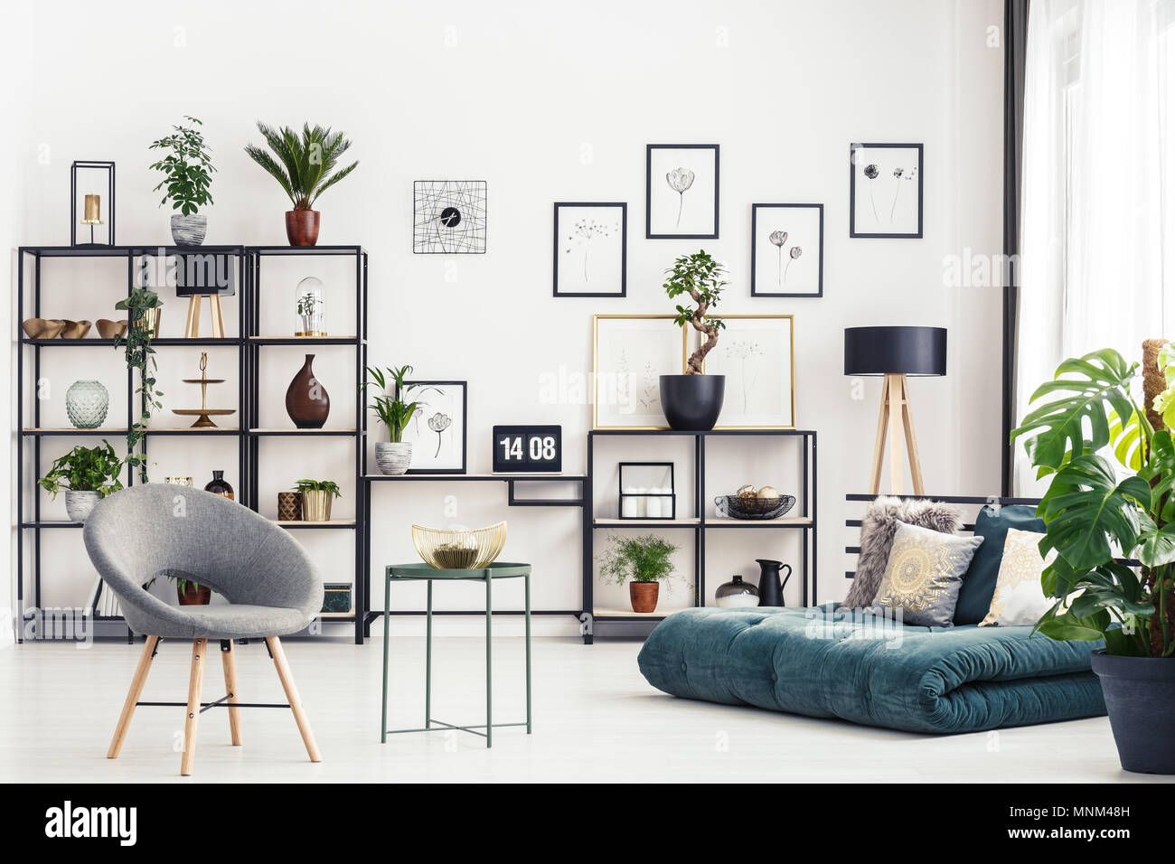 Entre Table fauteuil gris et vert futon dans home office interior with laptop on desk Photo Stock