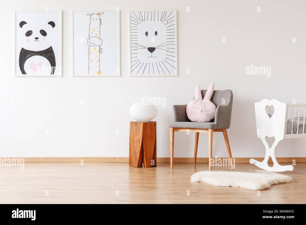 Lumière sur le tabouret en bois à côté de gray fauteuil avec coussin, lit bébé blanc et tapis chambre d'enfant avec galerie Banque D'Images