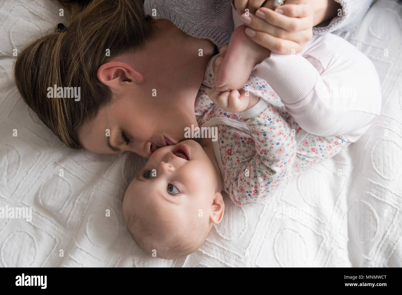 Mother kissing baby girl (18-23 mois) avec soin Photo Stock