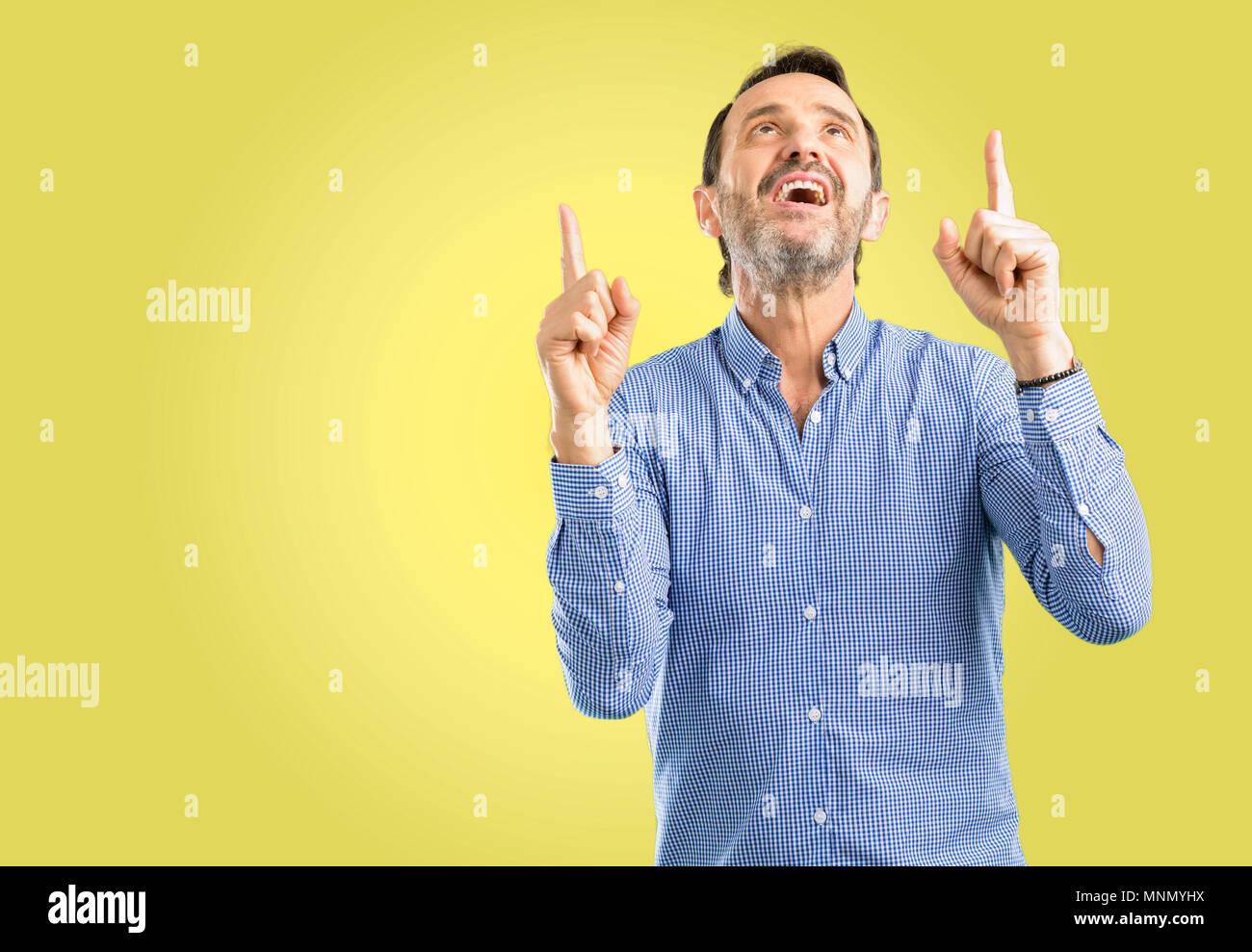 Beau moyen age homme heureux et surpris cheering pointant vers le haut Photo Stock