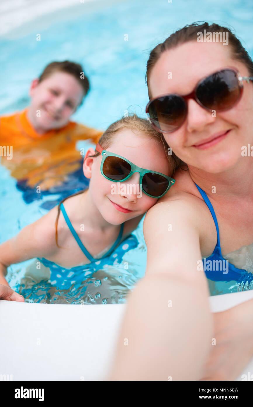 Heureux mère et ses enfants à l'extérieur piscine en tenant sur selfies vacances tropicales Banque D'Images