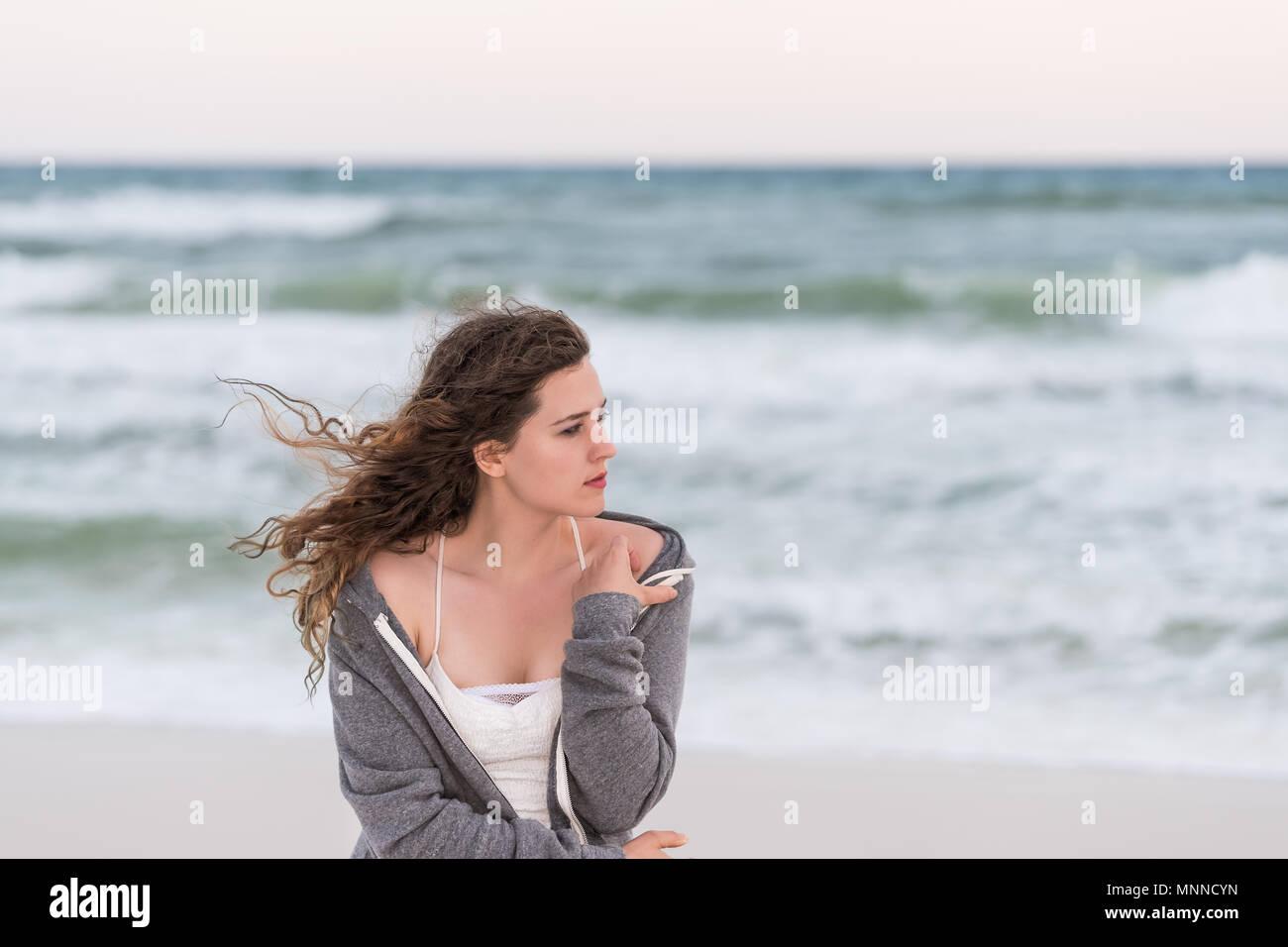 Jeune femme en grelottant de froid, pull robe blanche sur la plage coucher  du soleil 90344fdc925