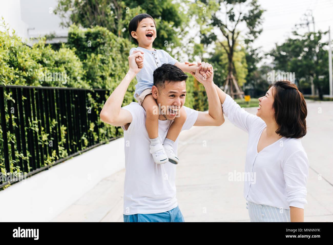Cute Asian père usurpation de son fils avec sa femme dans le parc. La famille excité les mains avec bonheur Banque D'Images