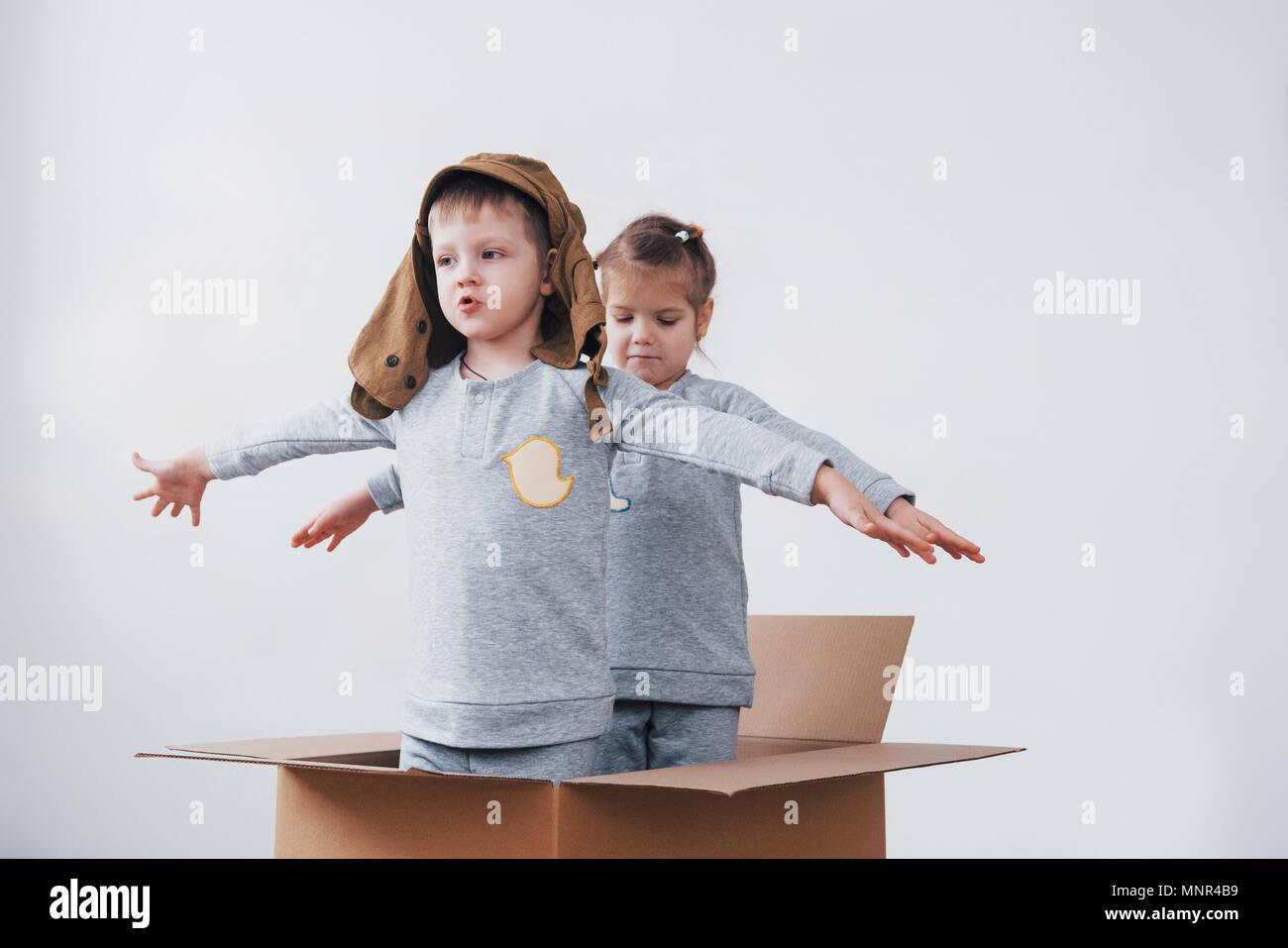 La petite enfance ludique. Petit garçon s'amuser grâce à la boîte de carton. Garçon prétendant être pilote. Little Boy and girl having fun at home Banque D'Images