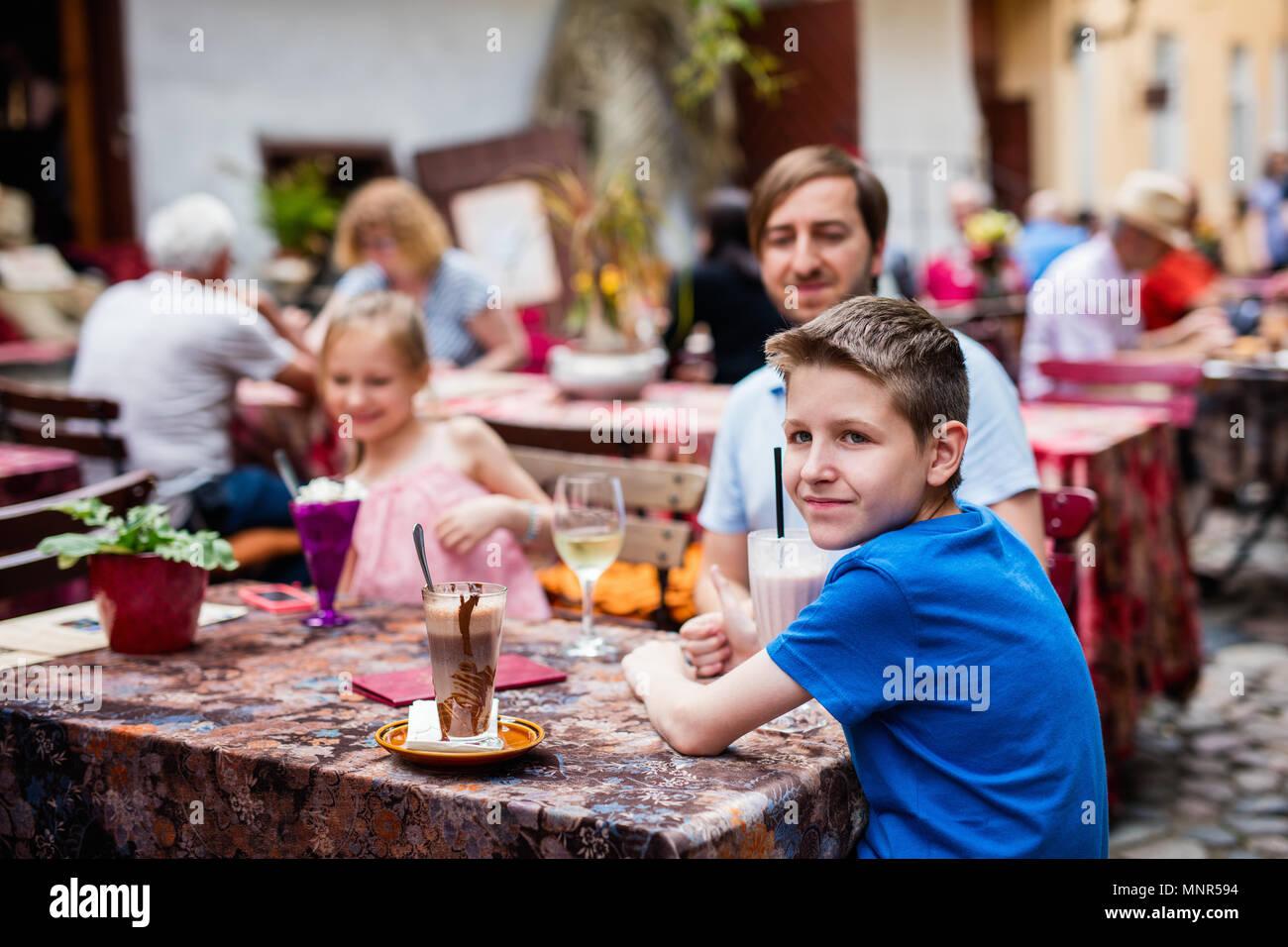 Le père et ses enfants au café en plein air sur la journée d'été Photo Stock