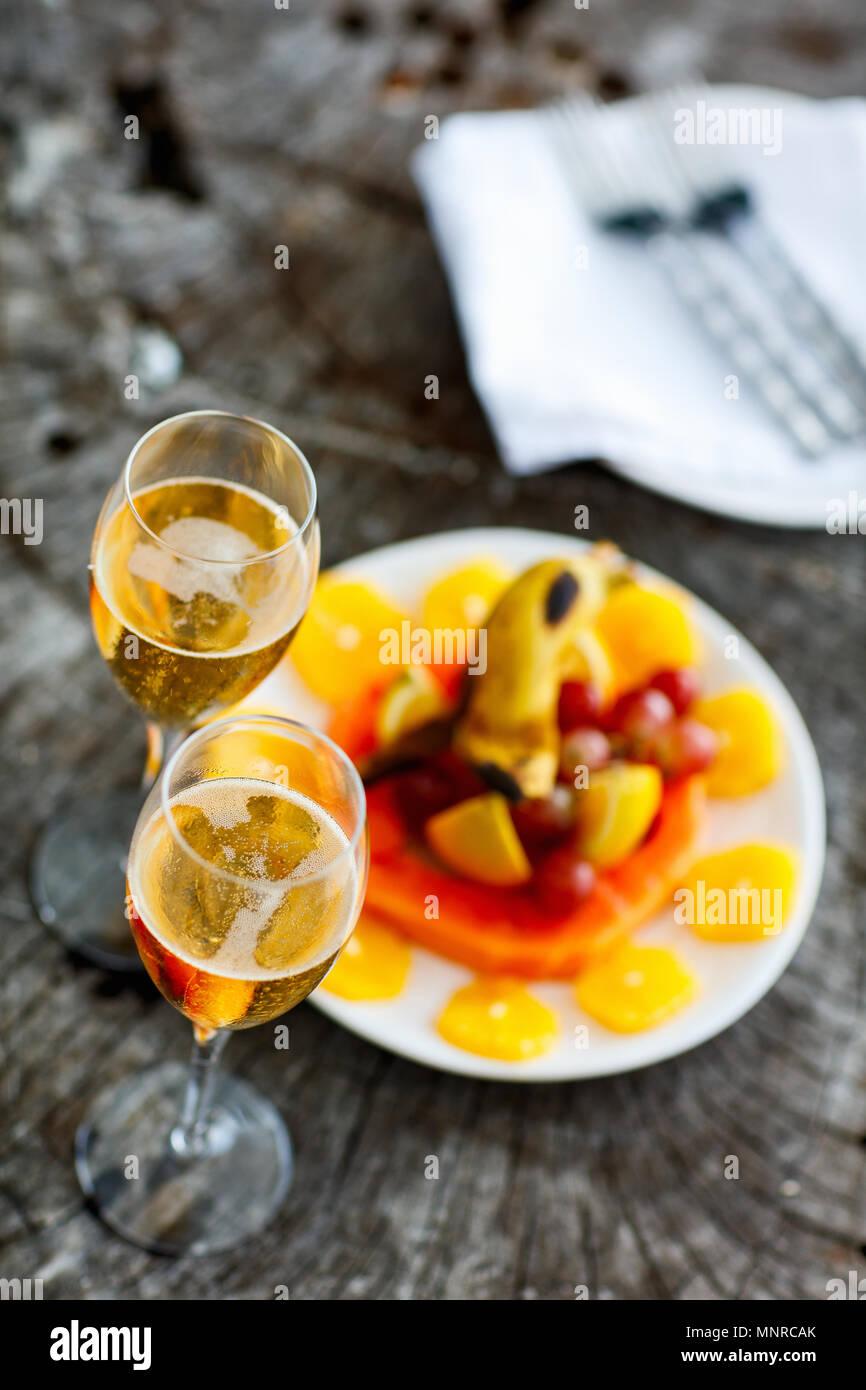 Deux verres avec du champagne et des fruits sur le plateau en bois vintage servi pour une occasion spéciale ou une fête Photo Stock