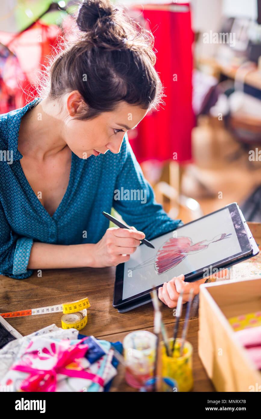 Créateur de mode de dessin d'un nouveau modèle sur une tablette numérique Photo Stock