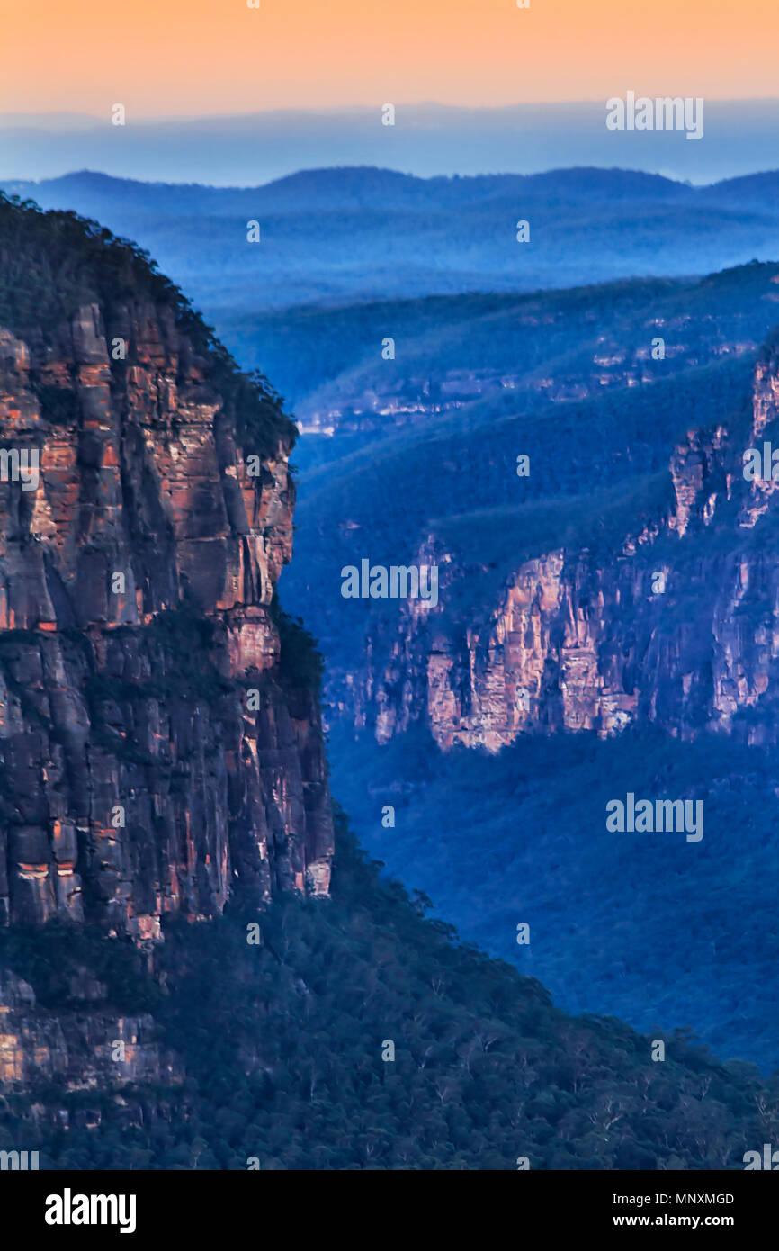 Fragment de falaises de grès érodées dans les Montagnes Bleues de l'Australie comme vu de Pulpit Rock lookout le long de Grand Canyon au coucher du soleil. Photo Stock