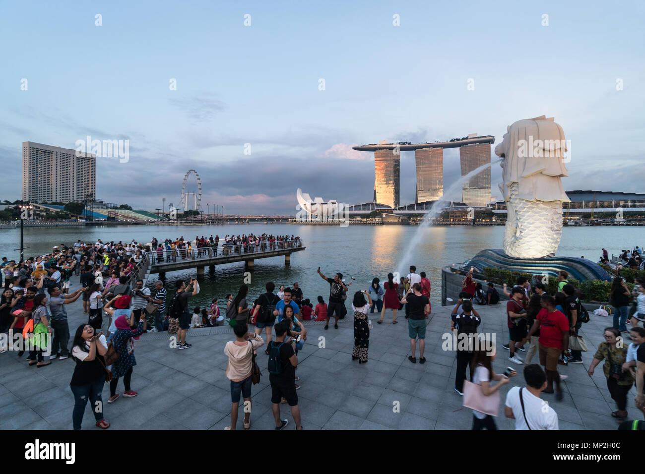 Singapour - 13 mai 2018: Une grande foule de touristes de prendre des photos et en selfies avant de la fontaine par Merlion le Marina Bay au coucher du soleil à Singapour Banque D'Images