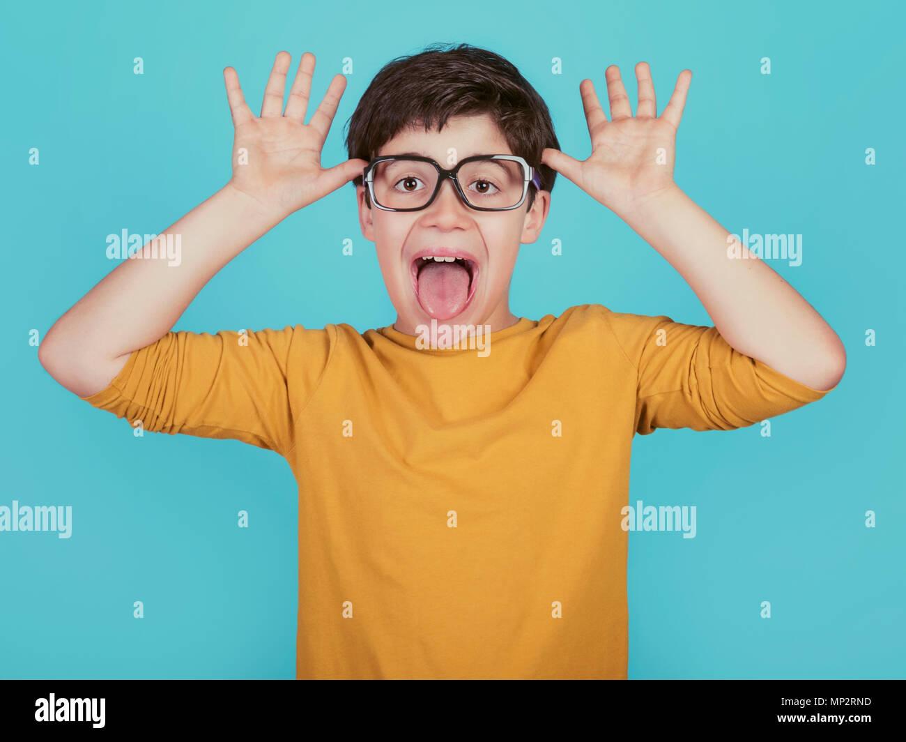 Funny boy avec des lunettes à montrer sa langue sur fond bleu Photo Stock
