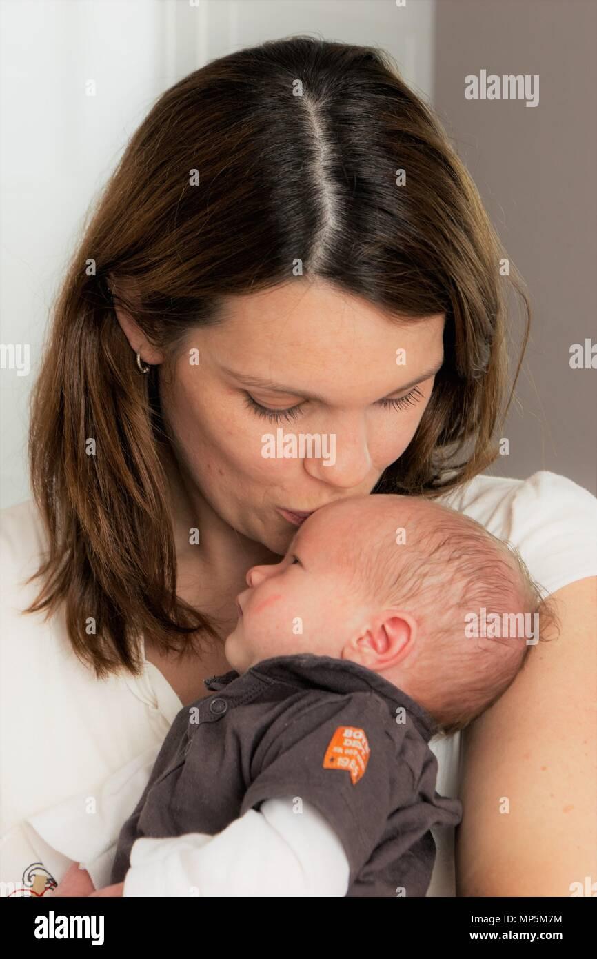 Maman apaiser son nebworn coliques bébé garçon à la maison. Photo Stock