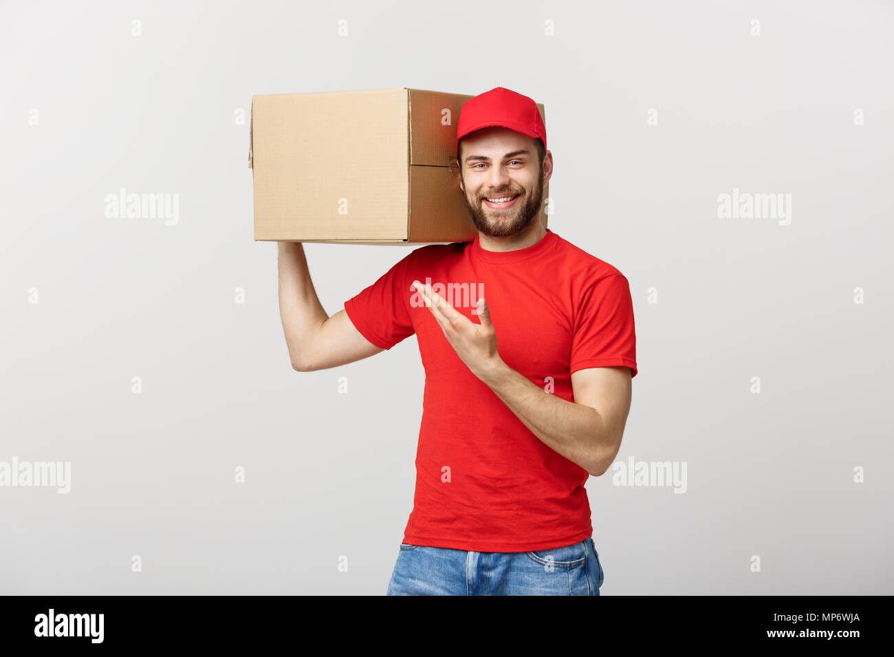 Concept de livraison - Portrait of Happy Young man faisant part de présenter un fort paquet. Isolé sur fond studio gris. Copier l'espace. Photo Stock