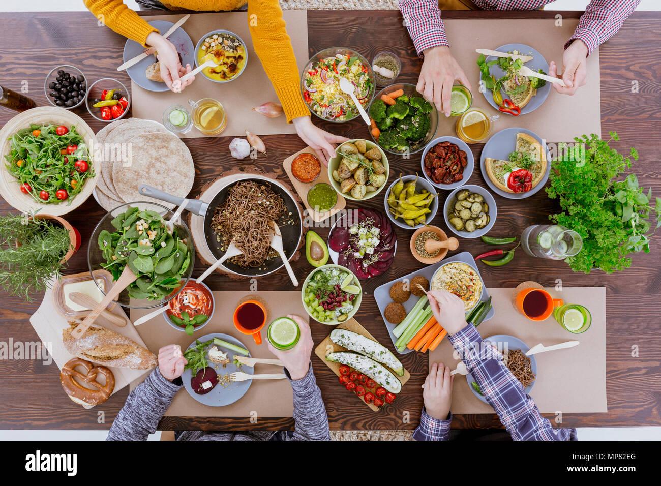 Les personnes ayant des légumes, repas assis à table commune bois Photo Stock