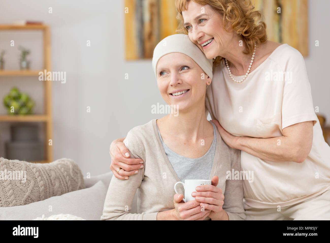 Femme heureuse avec écharpe aux prises avec la maladie avec l'aide de sa maman Photo Stock