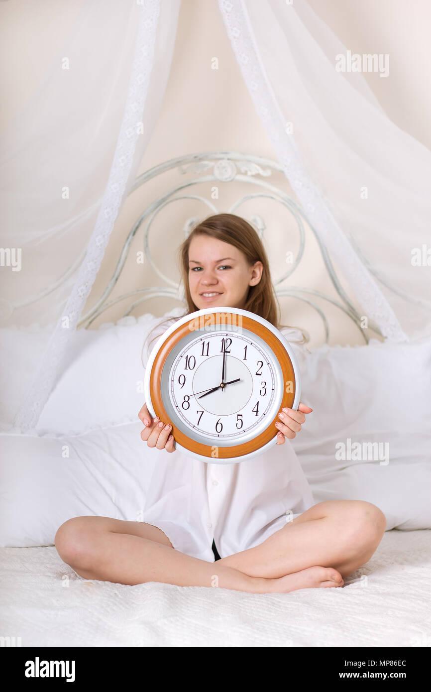 Femme Au Reveil belle jeune femme au lit et réveil banque d'images, photo stock