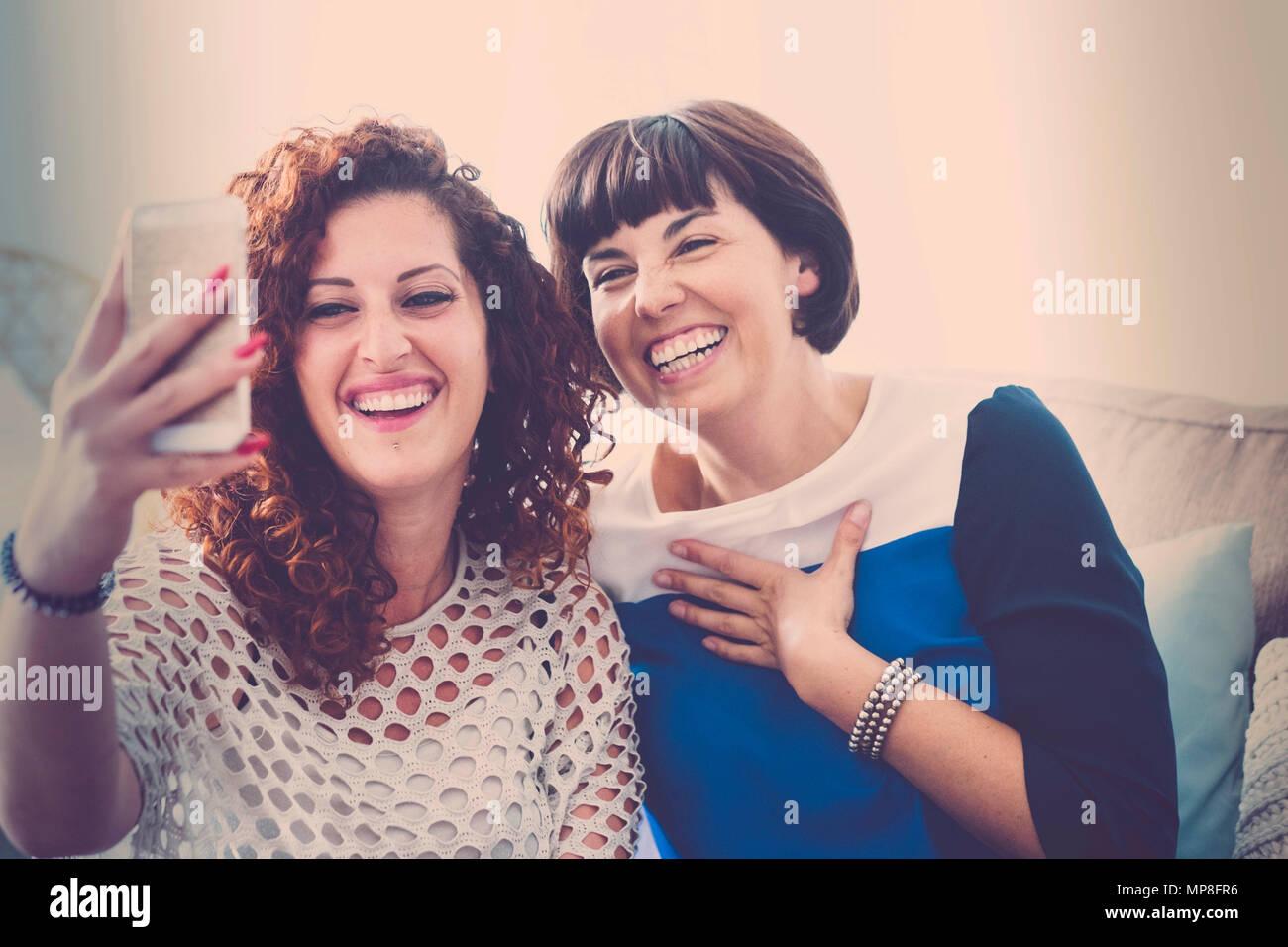 Appelez vos amis avec un téléphone mobile dans la vidéo en direct pour un couple de belles femmes d'âge moyen à la maison. communiquer et les gens connectés moderne concept. Photo Stock