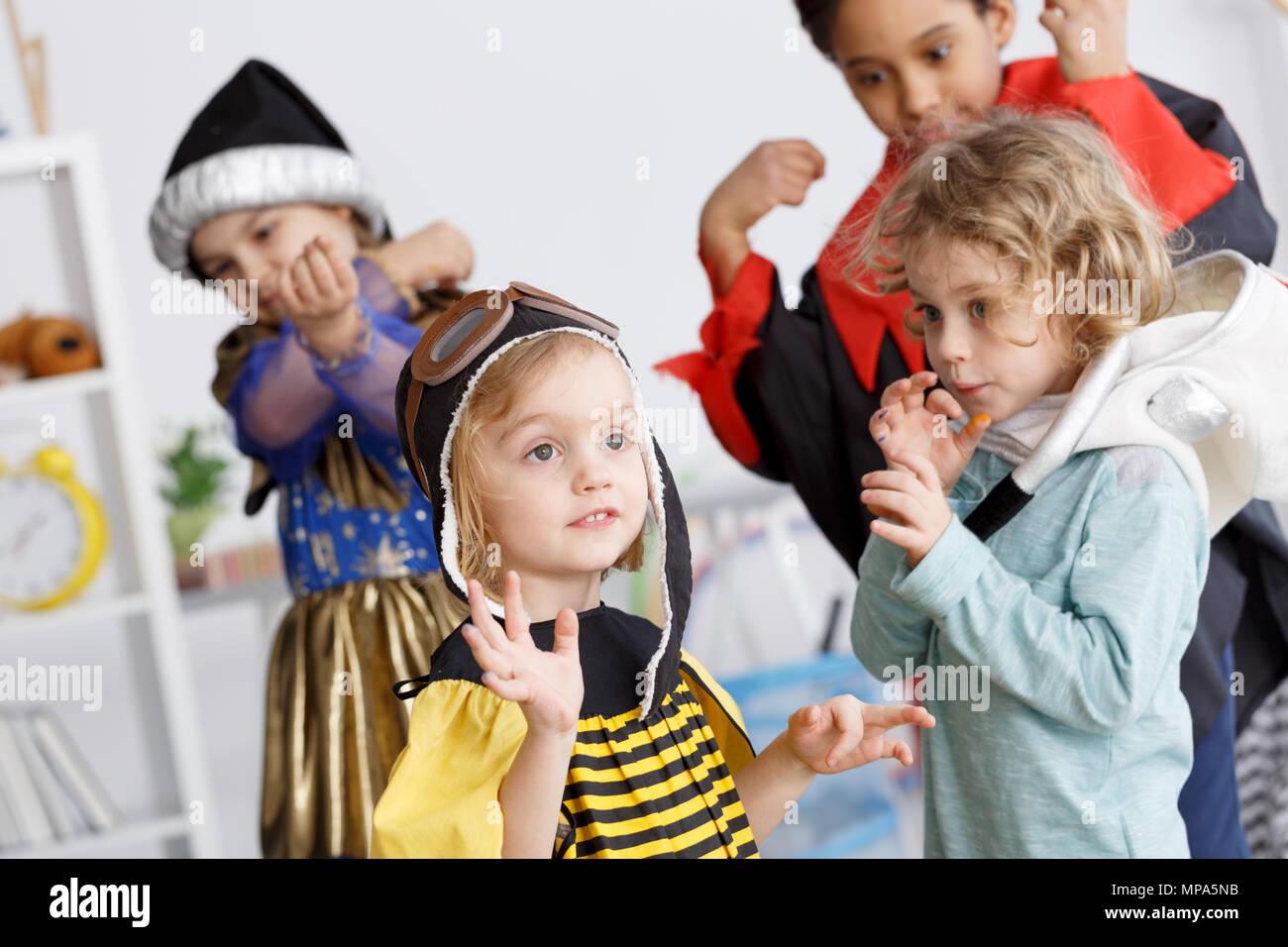 Les enfants en costumes colorés s'amusant sur la maternelle partie Photo Stock