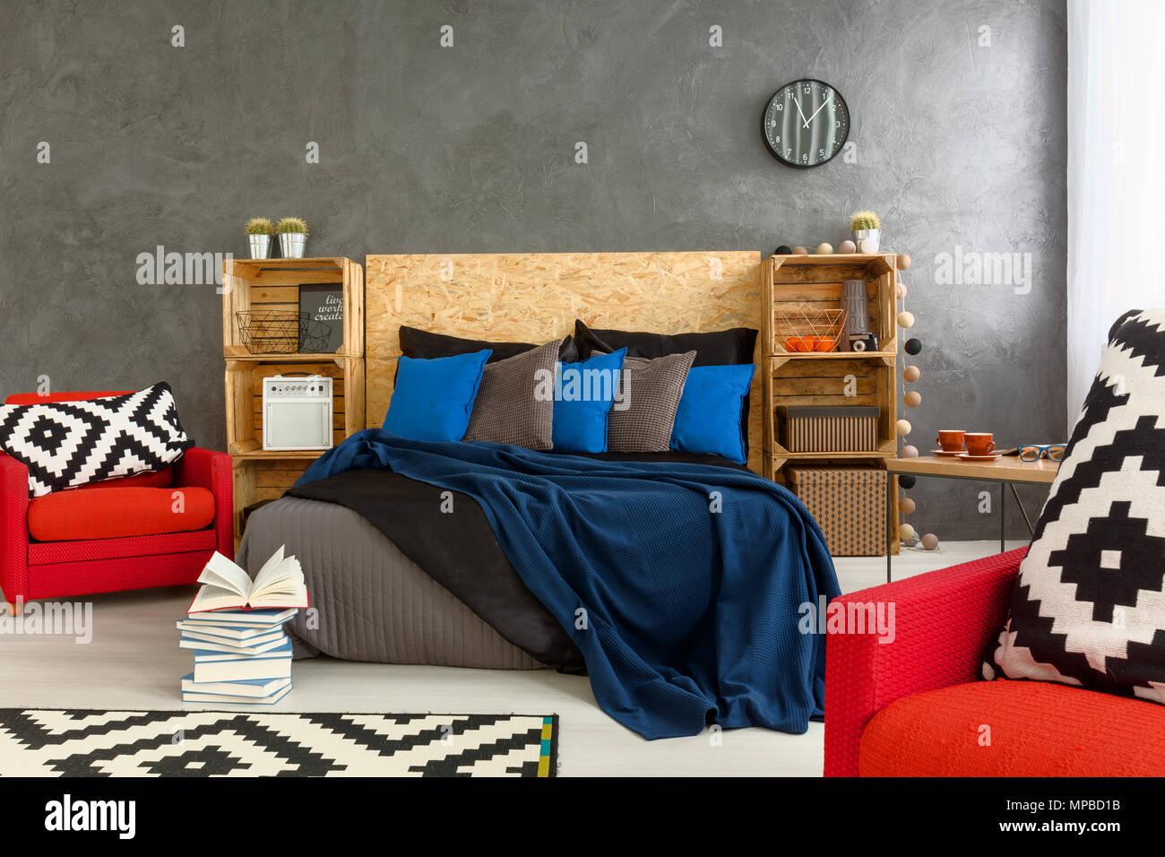 Chambre élégante avec des murs gris et rouge fauteuil avec peu de ...