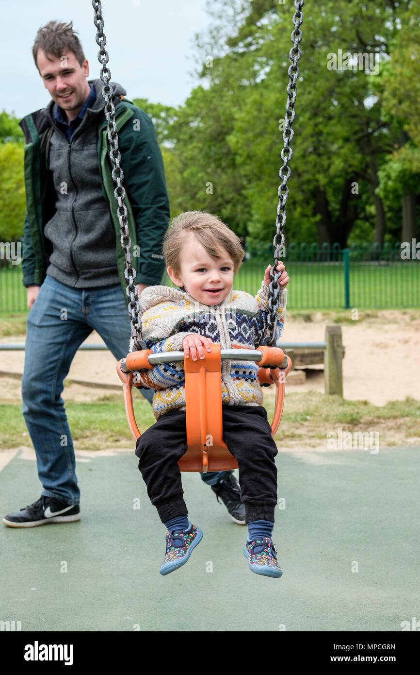 Père en poussant son fils de 18 mois sur une aire de swing Photo Stock