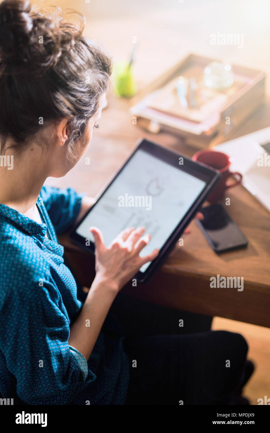 Vue de dessus. Une femme à l'aide d'une tablette numérique Banque D'Images