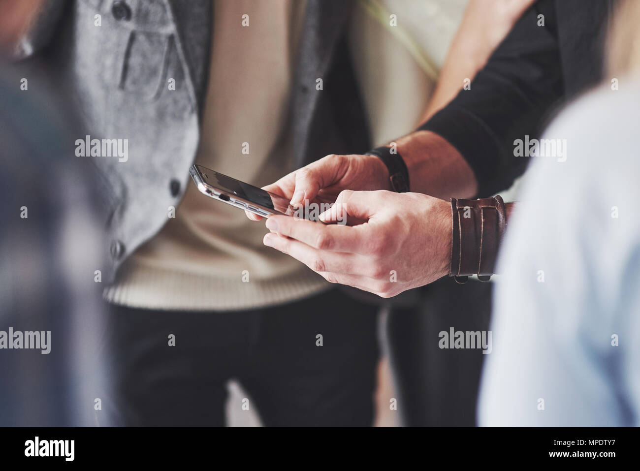 Close up young friends looking at smart phone while sitting in cafe. Les gens de race mixte restaurant en utilisant mobile phone Photo Stock