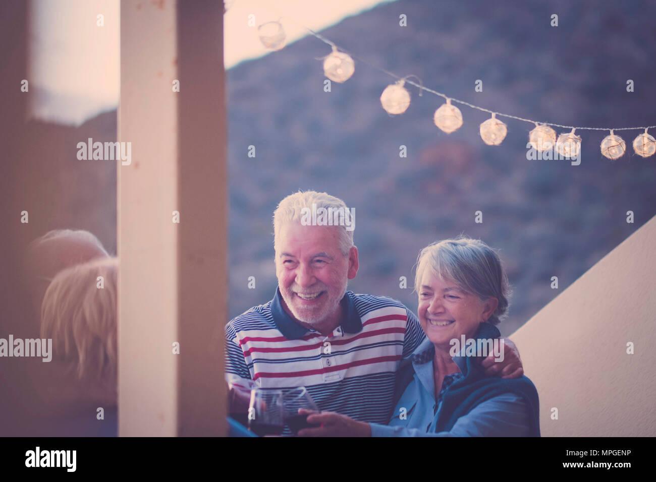 Terrasse extérieure avec une lumière dorée et quatre aînés adultes hommes et femmes restant ensemble avec joie et bonheur boire du vin ensemble Photo Stock