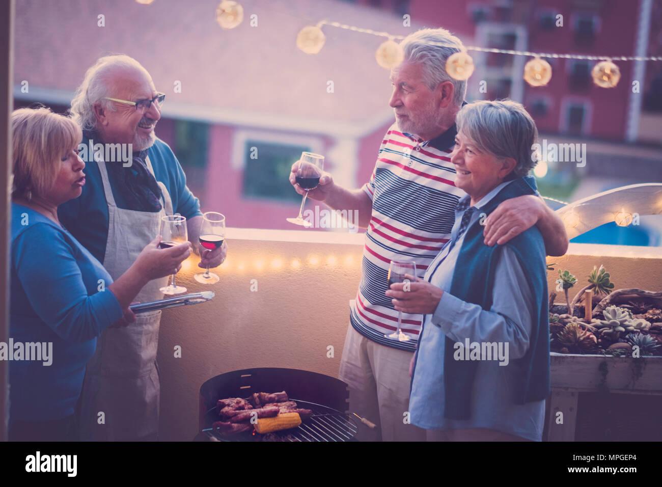 Groupe d'amis, les aînés ayant un barbecue barbecue ensemble sur le toit avec vue magnifique sur les autres bâtiments. Lumières dans la terrasse de l'ampoule et sourire ha Photo Stock