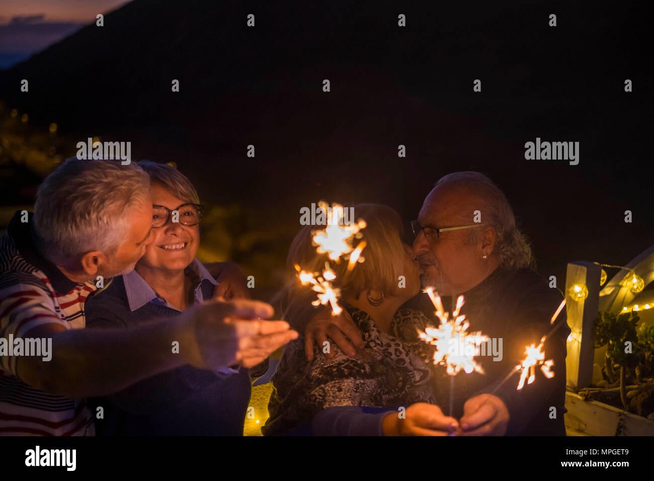 Deux couple baiser et célébrer un anniversaire ou événement comme nouvel an outdoor avec sparkles. le bonheur et l'espoir pour l'avenir. concept de vie senior r Photo Stock