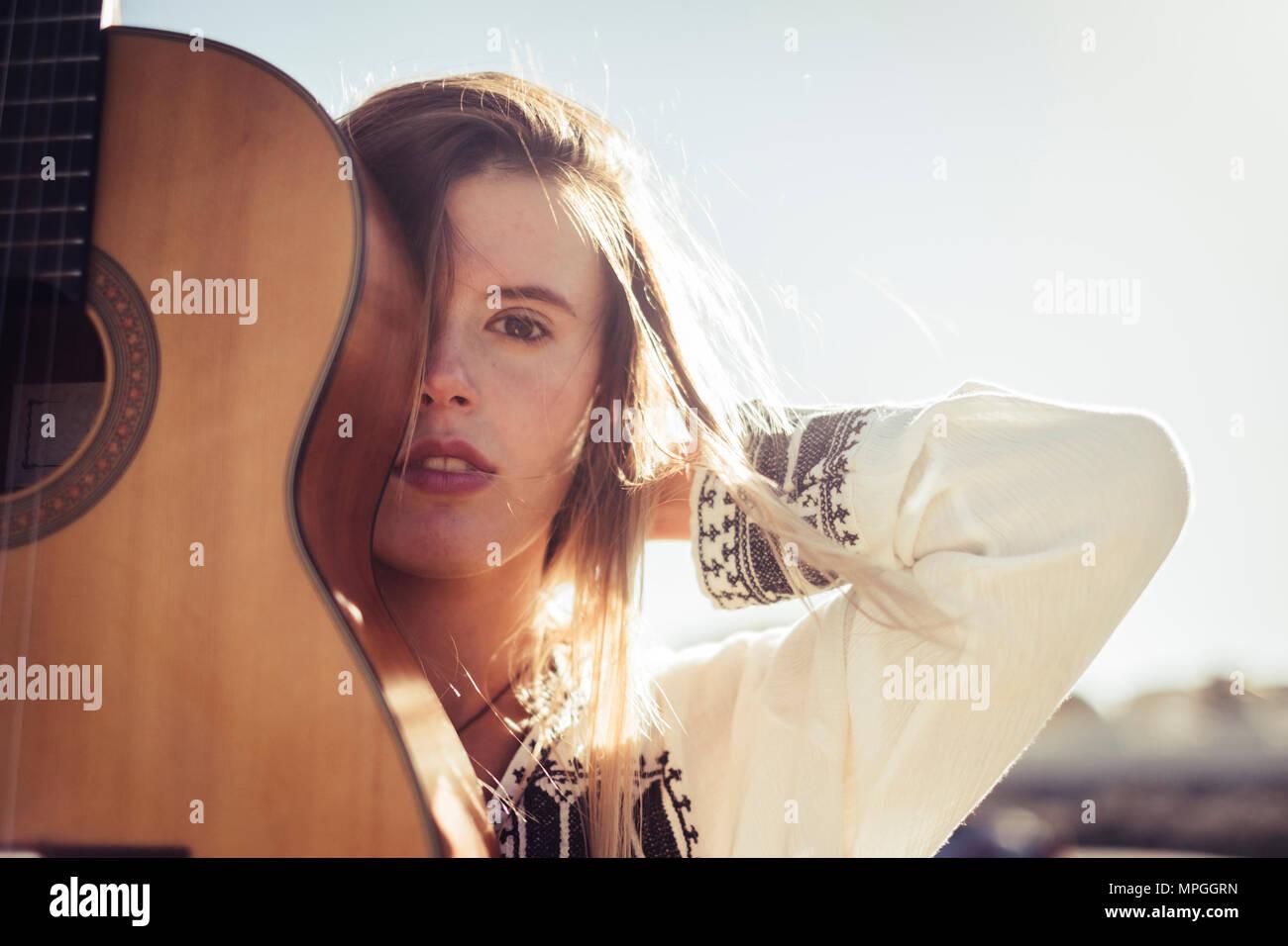 Les sorties en plein air et rebelle, wanderlust concpet avec jolie blonde woman avec une guitare acoustique profiter de l'endroit et le billet Photo Stock