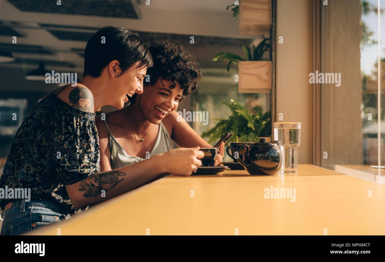 Deux jeunes femmes à l'aide d'un smart phone at coffee shop. Deux amis femme à l'aide d'un téléphone mobile à un restaurant. Banque D'Images