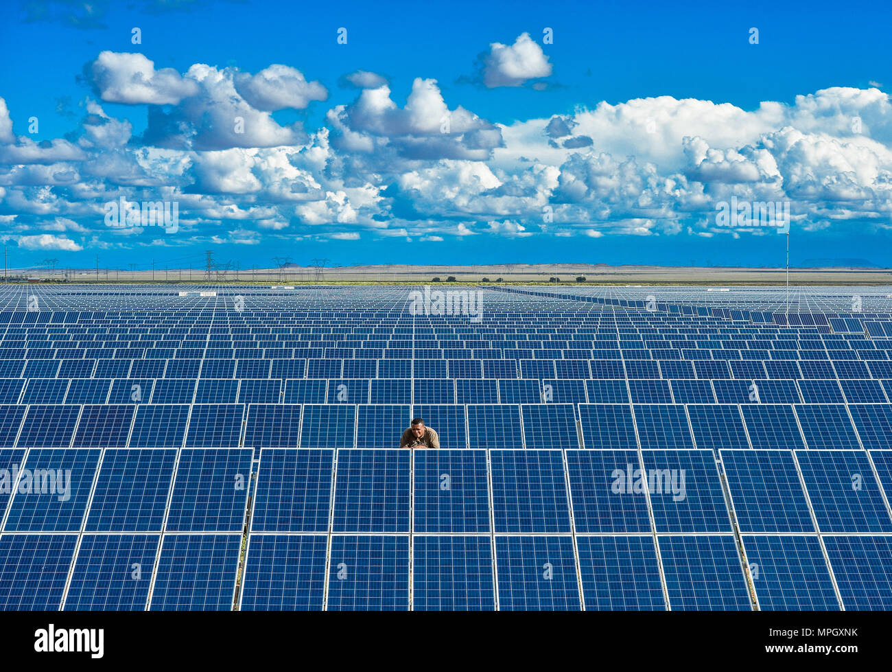 Un homme vérifie les panneaux solaires sur une ferme solaire en Afrique du Sud Photo Stock