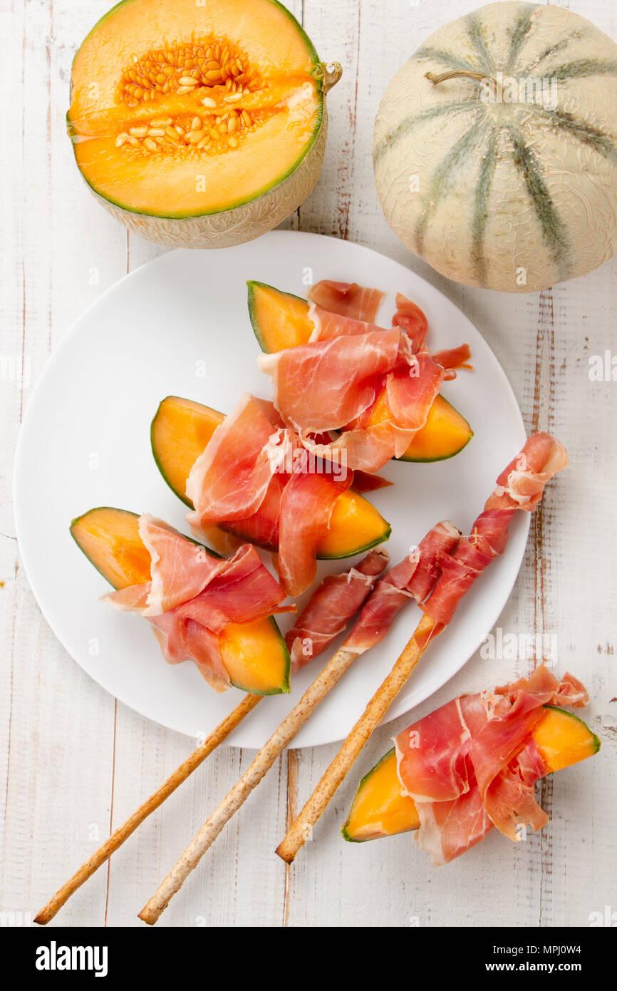 Melon cantaloup avec du jambon, un apéritif italien et espagnol traditionnel servi avec aliments complets grissini Photo Stock