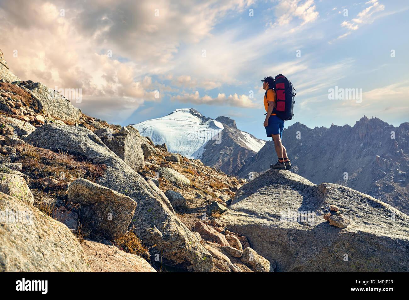 Randonneur dans une chemise orange avec de gros sac à dos à la recherche sur le sommet enneigé à l'arrière-plan Photo Stock