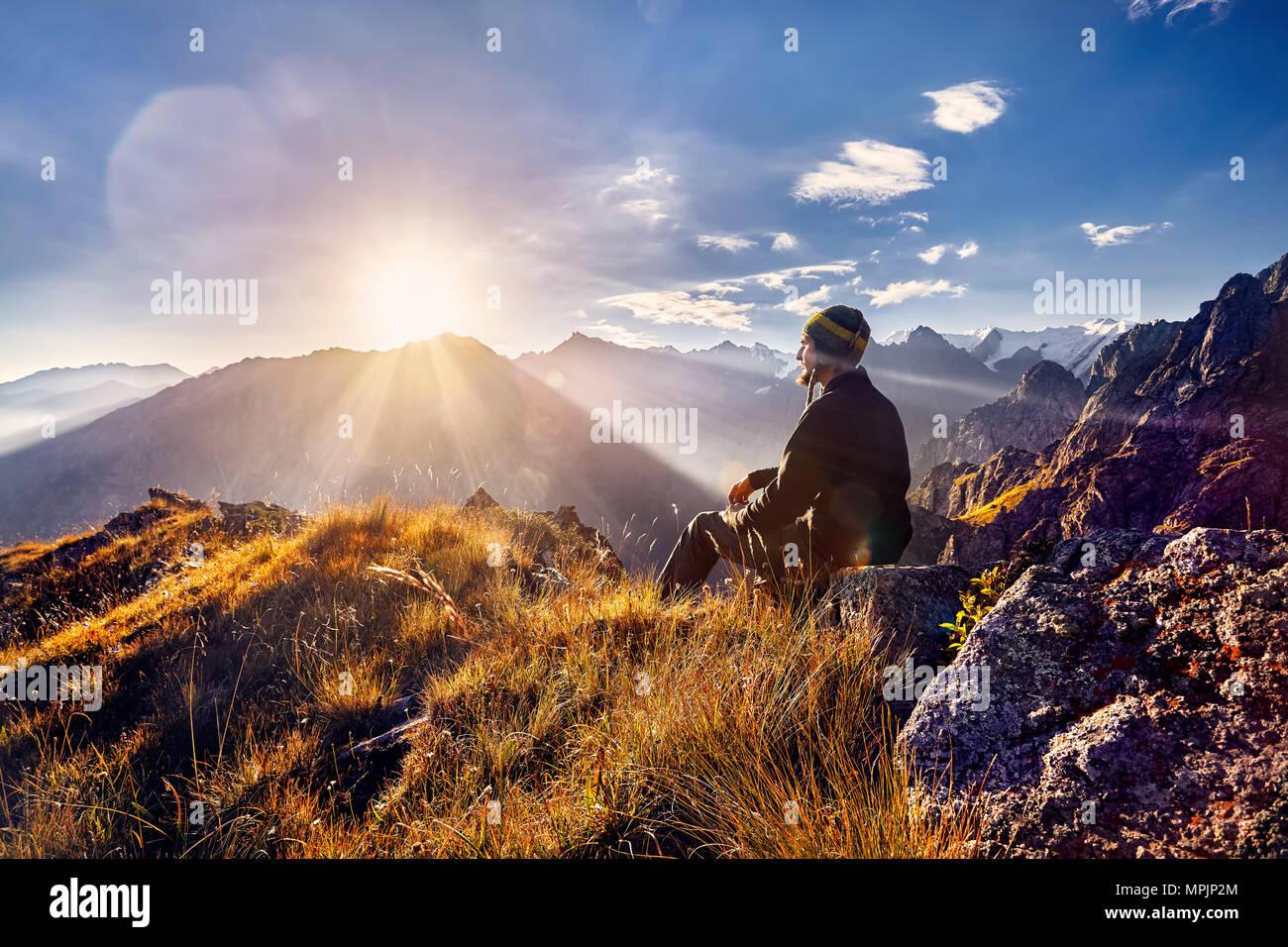 En népalais touristiques hat assis sur la colline et en regardant le lever du soleil dans les montagnes Photo Stock