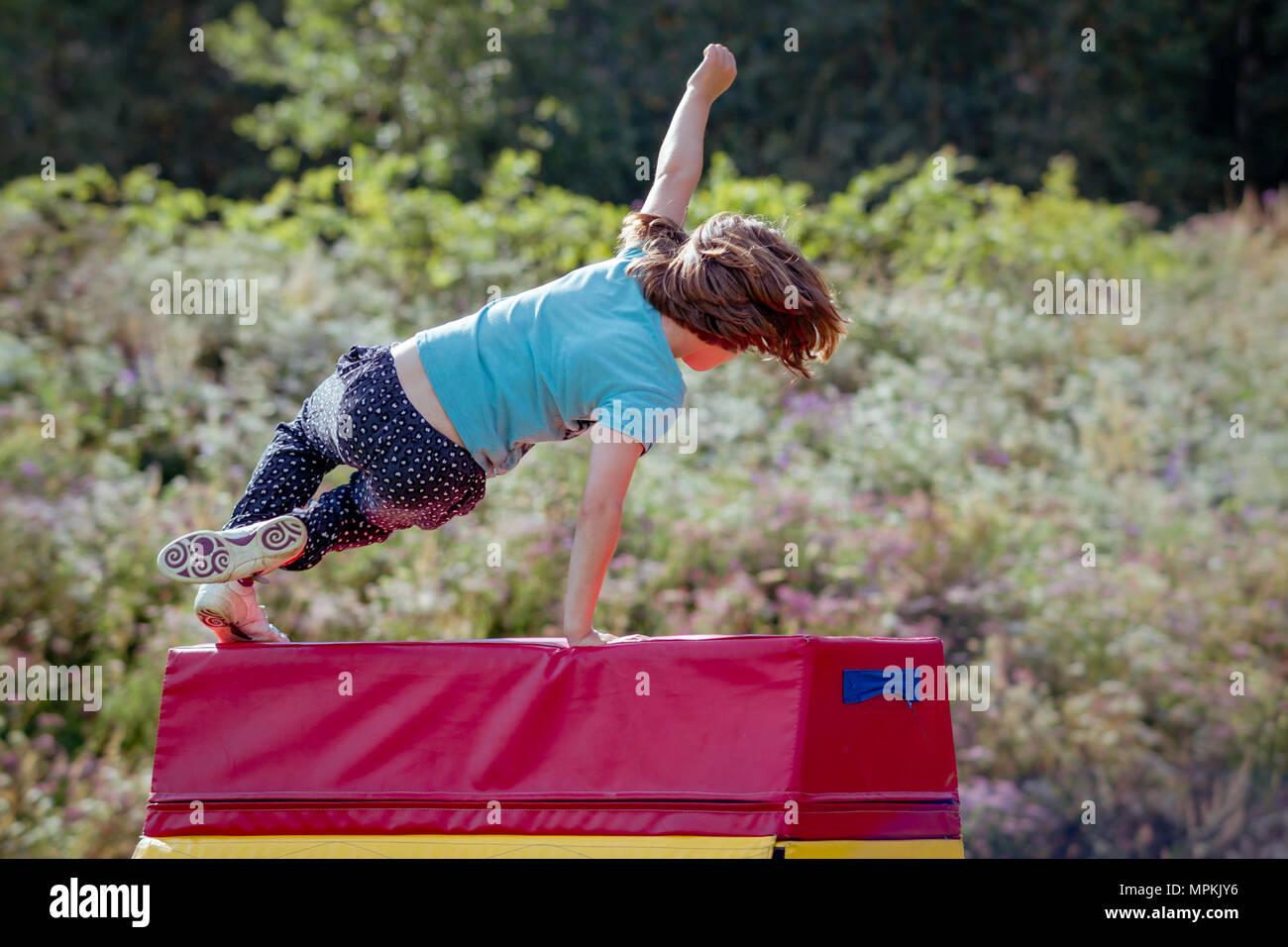 Petite fille pratique (pratique) en dehors de la gymnastique sur cheval de saut Photo Stock