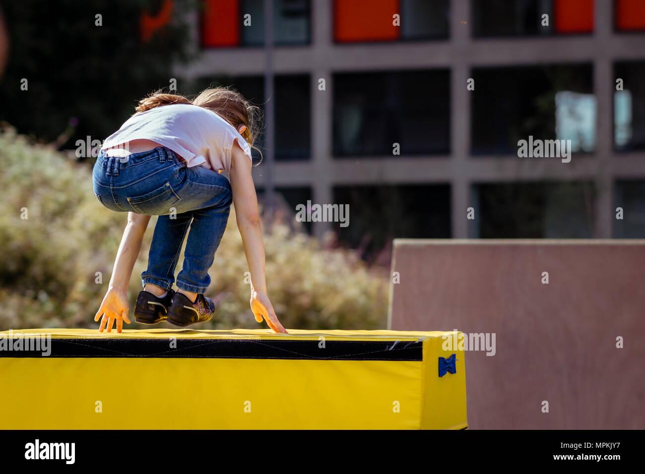 Petite fille pratique (pratique) en dehors de la gymnastique Parkour sur cheval de saut Photo Stock